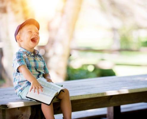 lachend jongetje met boek op schoot