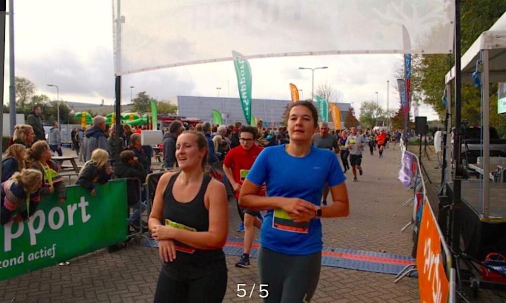 twee hardlopers die na de finish op hun horloge drukken