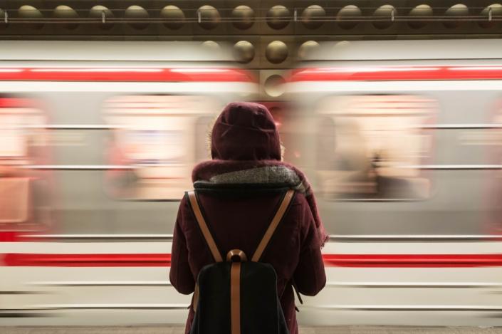 persoon in winterjas staat voor langsrijdende metro