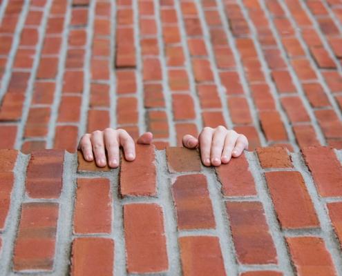 bakstenen muur waaraan stee handen zich vastklampen
