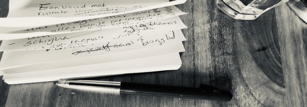 Een volgeschreven stapel geeltjes met pen ernaast