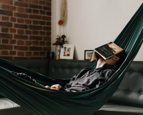 Man ligt in een hangmat met een boek op het gezicht